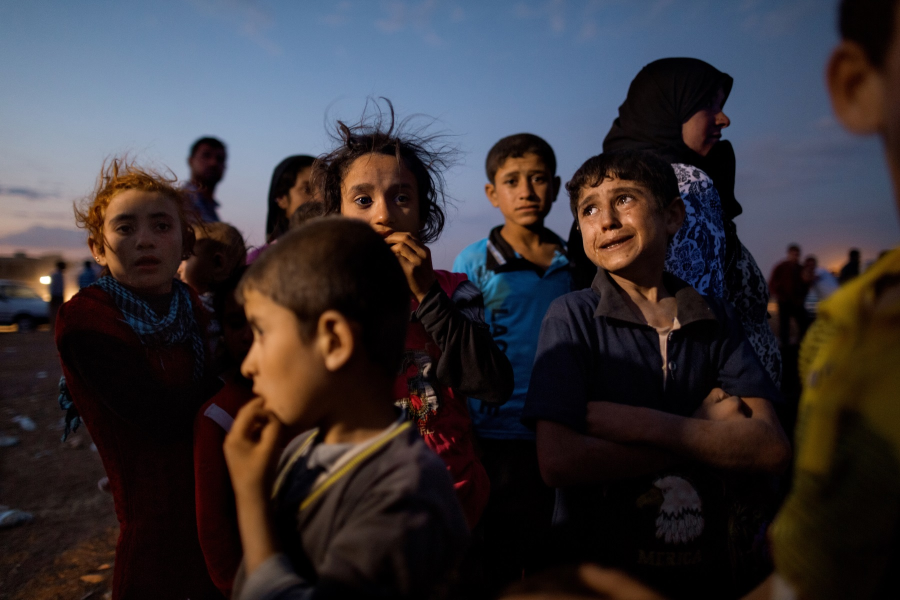 Ahmed, age 5, (right) cries out of fear after crossing into Turkey from Syria with his family Saturday night. Tens of thousands of Kurds fled an Islamic State assault on Kobani in Syria and stream across the border into the Turkish town of Dikmetas on Saturday, September 20, 2014. This was day two of the exodus when 200,000 Syrian's, mostly Kurds, crossed into Turkey in 72 hours.