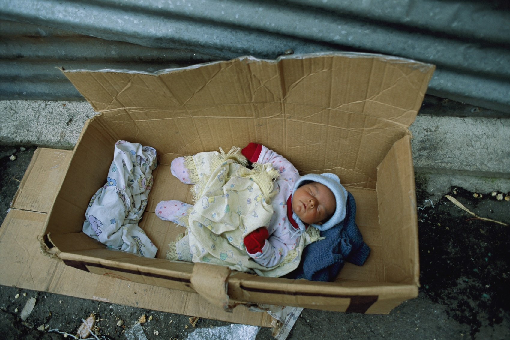 A baby sleeps inside a cardboard box that serves as a cradle.