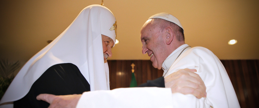 Pope Francis (R) and the head of the Russian Orthodox Church, Patriarch Kirill, greet each other during a historic meeting in Havana on February 12, 2016. Pope Francis and Russian Orthodox Patriarch Kirill kissed each other and sat down together Friday for the first meeting between their two branches of the church in nearly a thousand years. Francis, 79, in white robes and a skullcap and Kirill, 69, in black robes and a white headdress, exchanged kisses and embraced before sitting down smiling for the historic meeting at Havana airport.   AFP PHOTO / MAX ROSSI / POOL / AFP / POOL / Max ROSSI        (Photo credit should read MAX ROSSI/AFP/Getty Images)