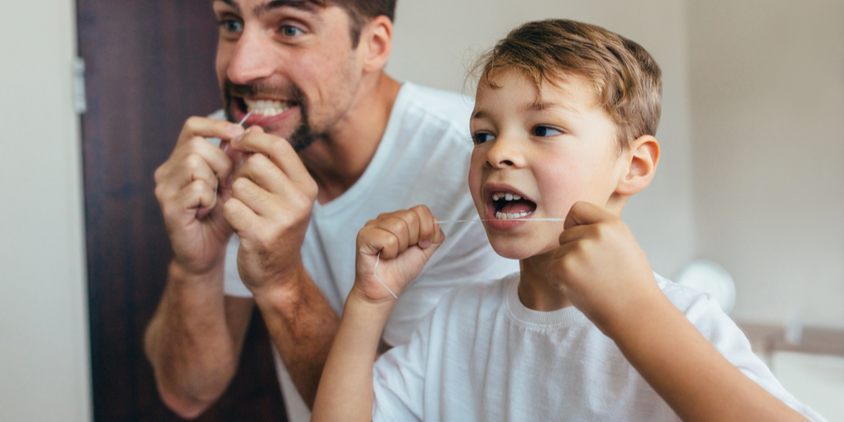 little boy with his father cleaning teeth