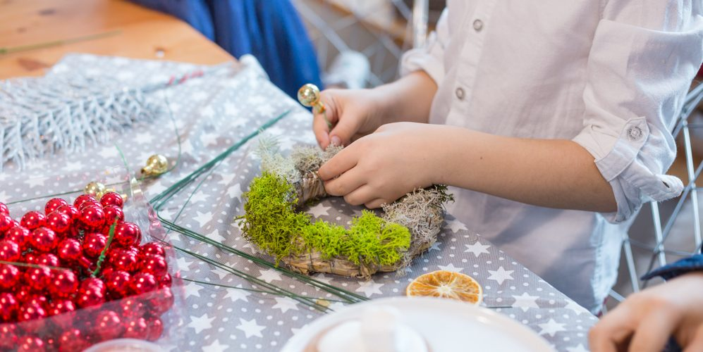 CHILD MAKING ADVENT WREATH